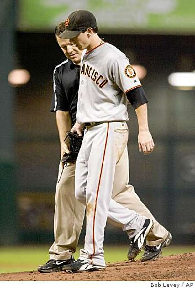 San Francisco Giants stater Tim Lincecum is assisted off the field by Giants head trainer Dave Groeschner after he was struck by a line drive off the bat of Houston Astros' Brad Ausmus in the fifth inning of a baseball game Tuesday, Aug. 12, 2008, in Houston. (AP Photo/Bob Levey) Photo: Bob Levey, AP