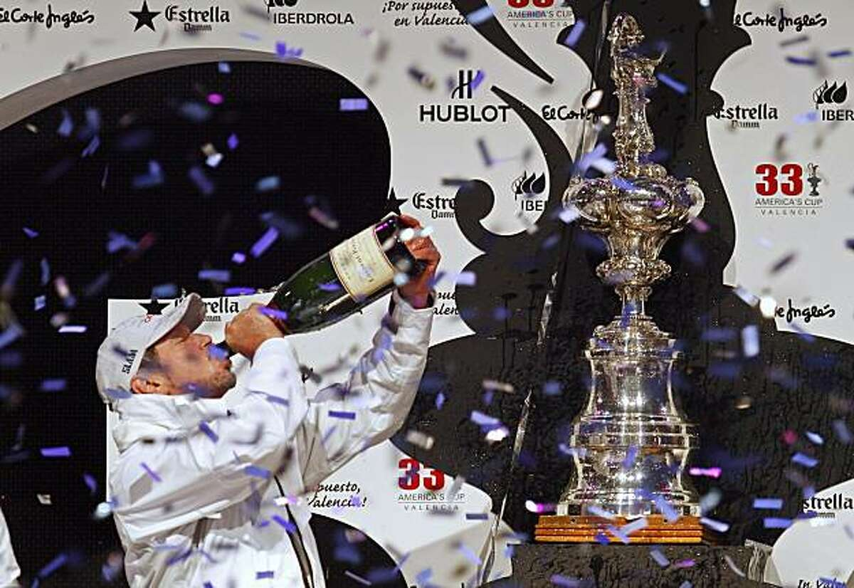 BMW Oracle Racing owner Larry Ellison drinks champagne on the podium after winning the 33rd America's Cup against Alinghi in Valencia, Spain, on Sunday, Feb. 14, 2010.