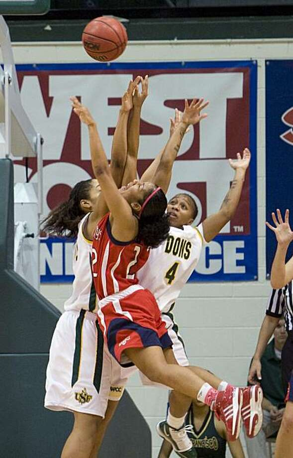 St. Mary's guard Jontelle Smith collides in midair with USF's Bailey Barbour and Brittany Brumfield, from left, as she goes for a layup at USF's home game against St. Mary's in San Francisco, Calif. on Saturday, Feb. 6, 2010. Photo: Adam Lau, The Chronicle