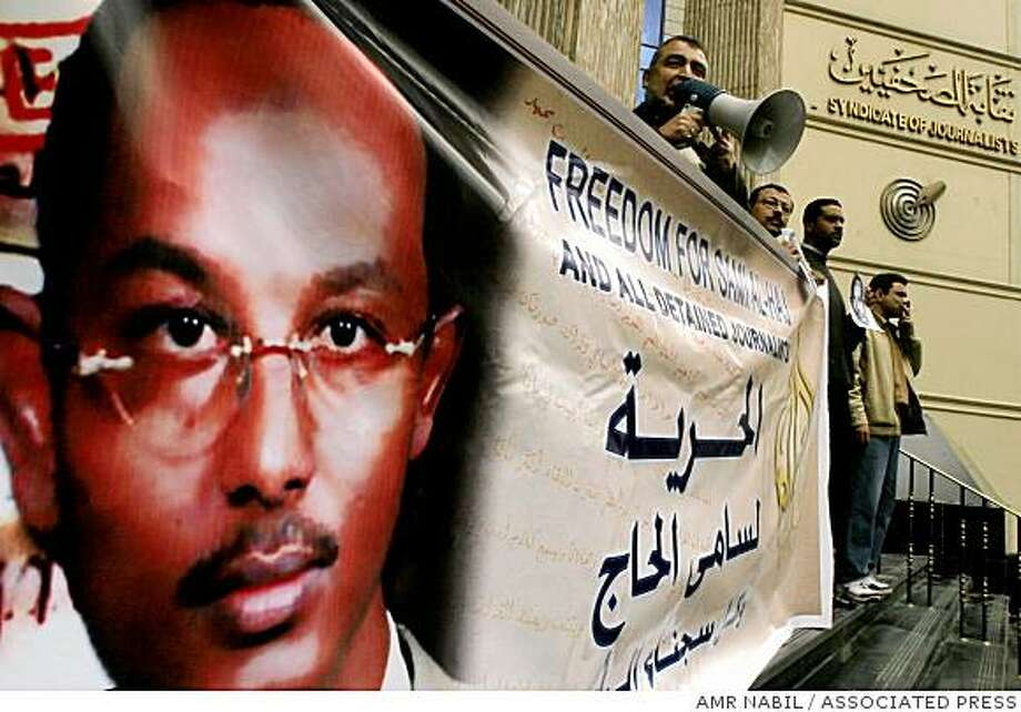 ** TO GO WITH GUANTANAMO HUNGER STRIKERS ** FILE ** Egyptian journalists hold a banner in Cairo, Egypt, in this  March 15, 2007 file photo supporting Al Jazeera cameraman Sami al-Hajj, a Sudanese national who was arrested by the US military while working for Al Jazeera during the US invasion of Afghanistan in 2001. The U.S. Military in Guantanamo has counted 24 men currently on hunger strike. A lawyer for a Guantanamo detainee says his client identified al-Hajj as one of the participants in the strike. (AP Photo/Amr Nabil) Photo: AMR NABIL, ASSOCIATED PRESS