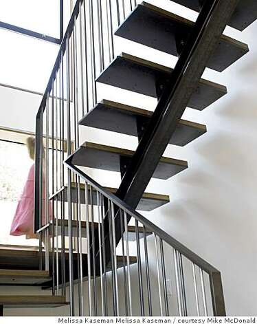 A switch-back staircase to the bedrooms upstairs was designed and built by Chris French Metal Fabrication in Oakland. The parts of the staircase are bolted- rather than welded-together. Welding consumes a lot of energy and the results are less fine says French. Photo: Melissa Kaseman Melissa Kaseman, Courtesy Mike McDonald