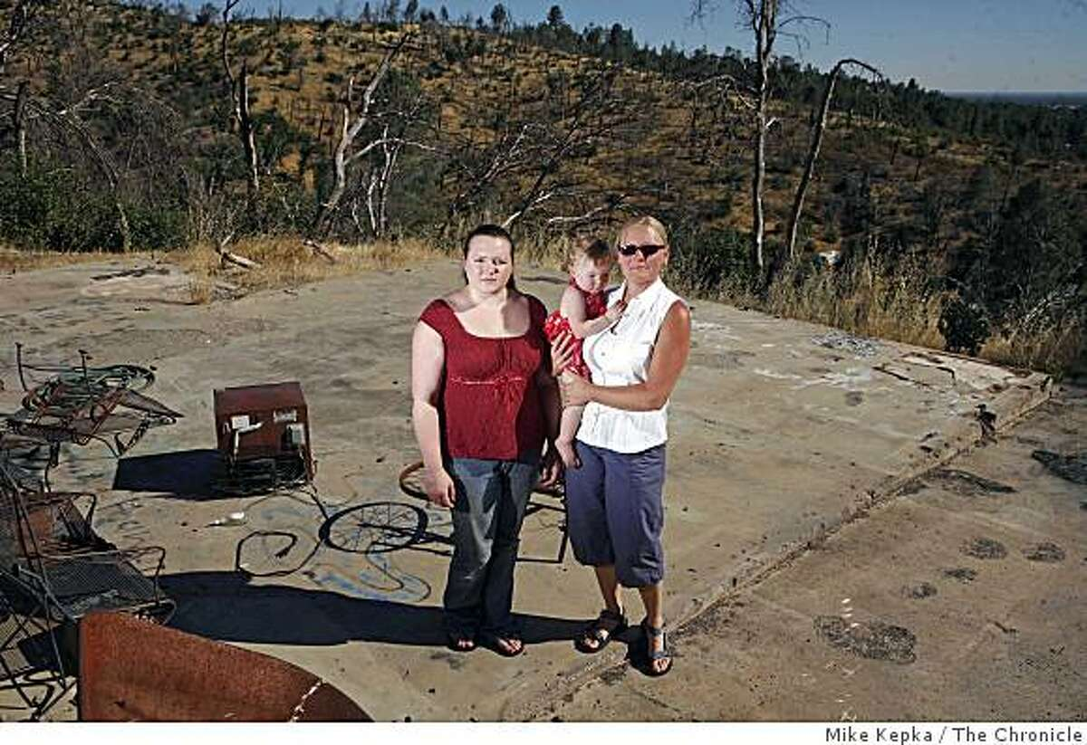 Four years after a fire destroyed their house in 2004, Rachelle Pinkerton, with her daughter Avilon Pinkerton, 16 months, and Sue Craite pose for a portrait on what remains of there burnt home on Monday, August 4, 2008 in Jones Valley, Calif.