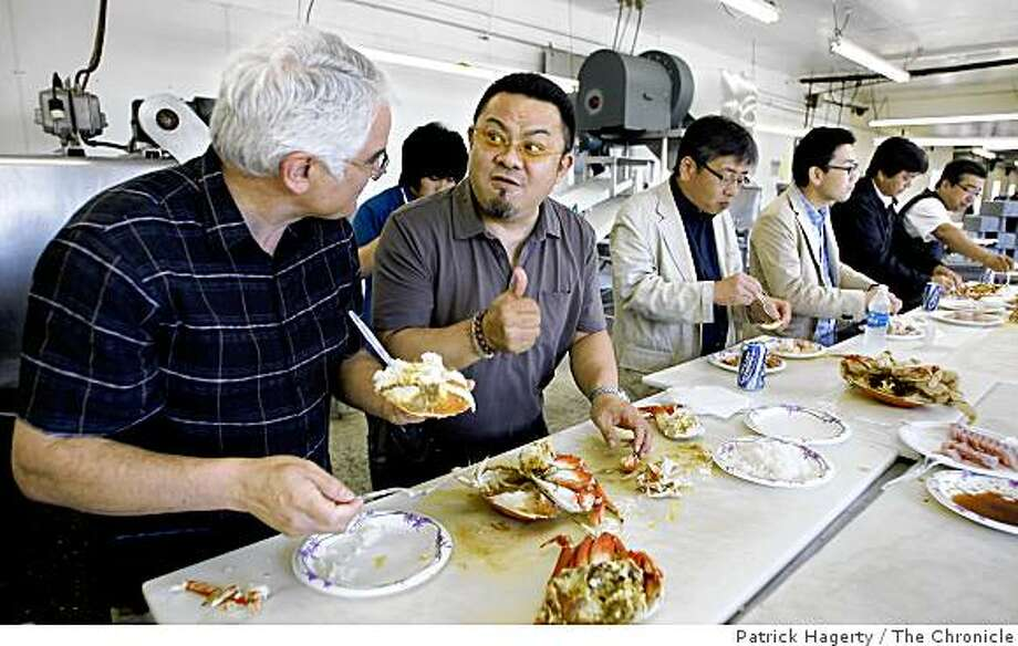 "Wild Planet co-founder and president, Bill Carvalho, left, gets a ""thumbs up"" from Osamu Shimizu, of Shizuoka, Japan, second from left, as they eat a lunch of fresh dungeness crab, from Prince Rupert, British Columbia and albacore tuna from Newport, Ore., Thursday, July 24, 2008, at Dungeness Development, a custom cannery, processor and packaging facility in South Bend, Wash. Shimizu was with a group of Japanese seafood distributors making an annual visit to seafood suppliers. (Others in the photos are: Yusuke Shimizu, behind, Hisakazu Imoto, third from left, Hiroaki Kawasumi, third from right, Yasuhiro Suzuki, second from right and Takashi Nasa, far right.) Photo: Patrick Hagerty, The Chronicle"