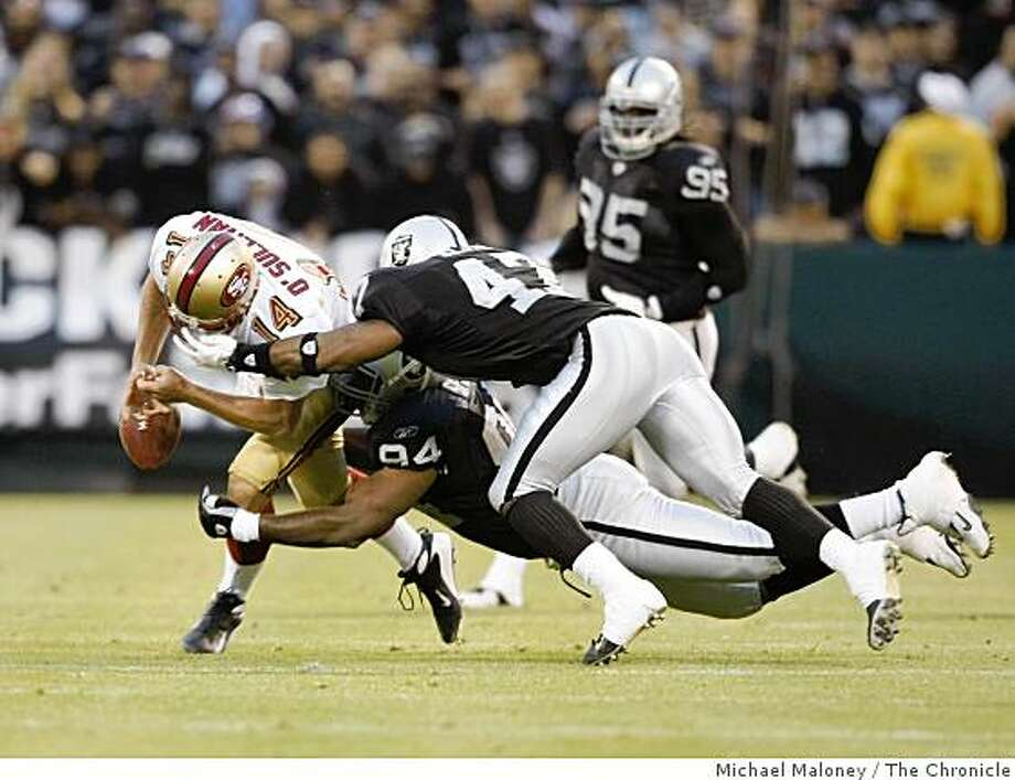 49ers quarterback J.T. O'Sullivan fumbles the ball in the second quarter, tackled by Raiders Greg Spires and Jon Alston. The Raiders recovered the fumble. Photo: Michael Maloney, The Chronicle