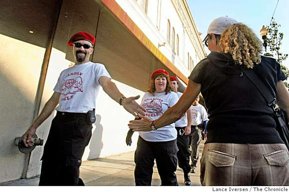 Oakland resident Vicki Beggs gives the Guardian Angels a high five as they walk down Oakland's Grand Ave Friday night.