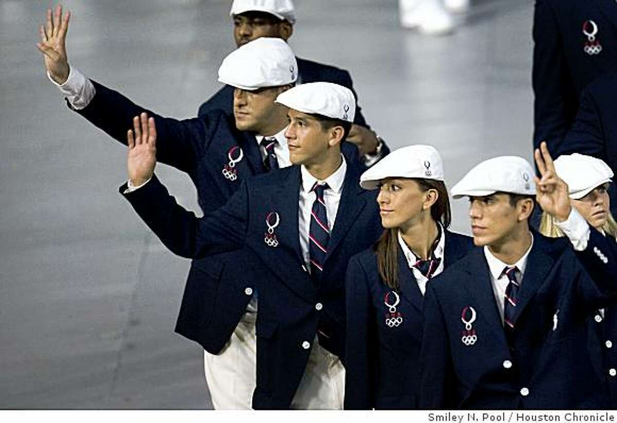US Taekwondo athletes, from right, Steven Lopez, Diana Lopez, Mark Lopez and team coach Jean Lopez wave as they enter the National Stadium, also known as the Bird's Nest, during opening ceremonies for the 2008 Summer Olympic Games.