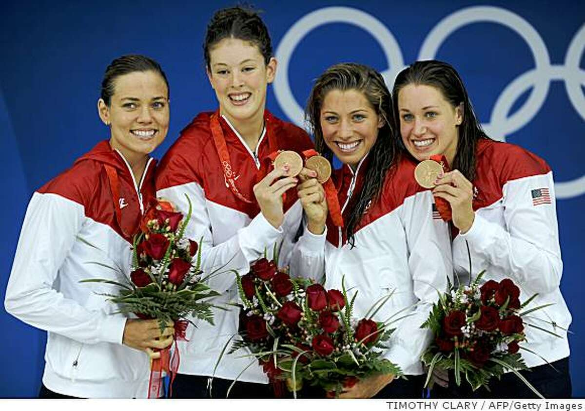 Bronze medalist from the US Natalie Coughlin (L), Allison Schmitt (2nd L), Caroline Burckle (2nd R) and Kathryn Hoff pose with their medals on the podium during the women's 4 x 200m freestyle relay swimming medal ceremony at the National Aquatics Center during the 2008 Beijing Olympic Games in Beijing on August 14, 2008. Australia smashed the world record by almost six seconds in swimming away with the women's 4x200metres freestyle relay gold medal at the Beijing Olympics. The Australians set a blistering pace to hit the wall in seven minutes 44.31 seconds and wipe 5.78secs off the record of 7:50.09. China took the silver medal in 7:45.93 ahead of the US in 7:46.33. AFP PHOTO / TIMOTHY CLARY (Photo credit should read TIMOTHY CLARY/AFP/Getty Images)
