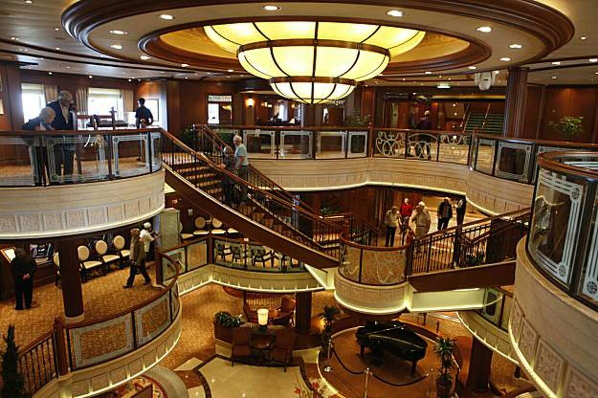 Passengers and visitors walk through the multi tiered Grand Lobby of Cunard's newest luxury liner, the Queen Victoria, which docked at pier 35 for a one-day-only visit on Wednesday January 27, 2010 in San Francisco, Calif. The ship, which has over 1,000 staterooms, a Royal Theater, a grand ballroom, and restaurants galore, is starting the first segment of its World Voyage and will be heading to Hawaii for the next leg of its trip.