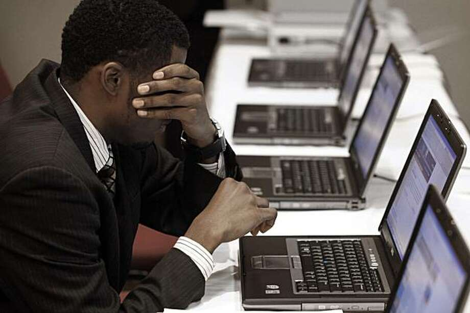 In this Nov. 4, 2009 photo,Terrell Collins, of Detroit, wipes his face while searching for employment on a laptop computer while attending a job fair in Livonia, Mich. The CEOs of America's largest companies said Tuesday, Dec. 8, 2009, that they do not expect employment to significantly improve in the next six months. (AP Photo/Paul Sancya) Photo: Paul Sancya, AP
