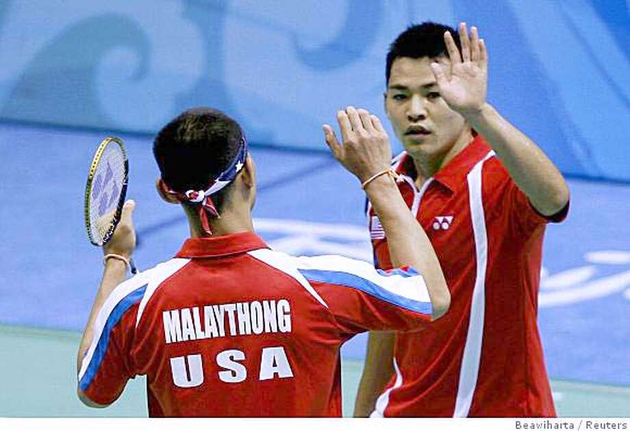 Howard Bach (R) and Bob Malaythong of the U.S. high-five each other after winning their men's doubles round of 16 badminton match against South Africa at the Beijing 2008 Olympic Games, August 12, 2008. Photo: Beawiharta, Reuters