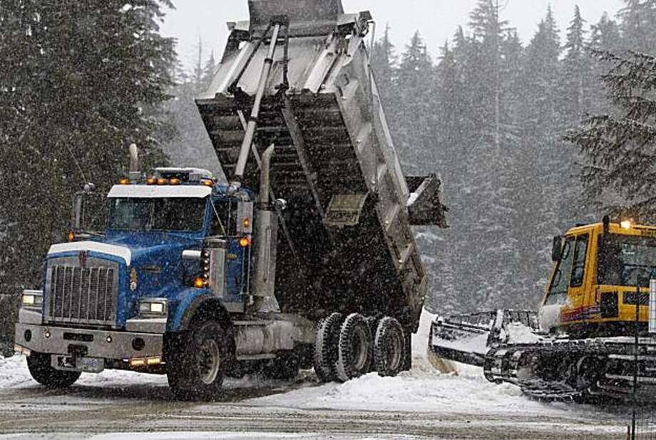 A dump truck delivers imported snow to the Cypress Mountain ski area in Vancouver, B.C. despite the region's first snowfall in weeks on Wednesday, Feb. 10, 2010. Cypress Mountain will host freestyle skiing events at the 2010 WInter Olympic Games which start on Friday. Paul Chinn/The Chronicle Photo: Paul Chinn, The Chronicle