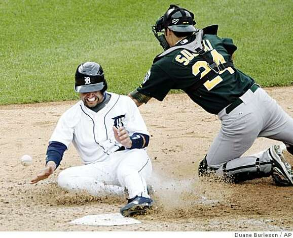 Detroit Tigers' Placido Polanco scores as the ball gets past Oakland Athletics catcher Kurt Suzuki in the eighth inning of a game Sunday, Aug. 10, 2008 in Detroit. Photo: Duane Burleson, AP