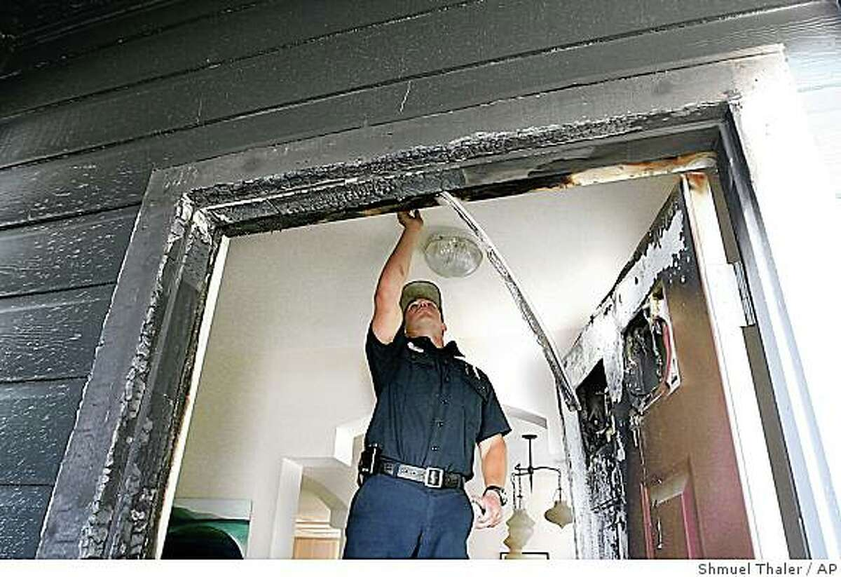 Santa Cruz firefighter Cody Muhly installs a new fire sprinkler at home on Village Circle in Santa Cruz, Calif. that was firebombed on Saturday, Aug. 2, 2008. The FBI is investigating two bombings that targeted university scientists, the latest in a rash of attacks against biomedical researchers who experiment on animals, authorities say. (AP Photo/The Sentinel, Shmuel Thaler)