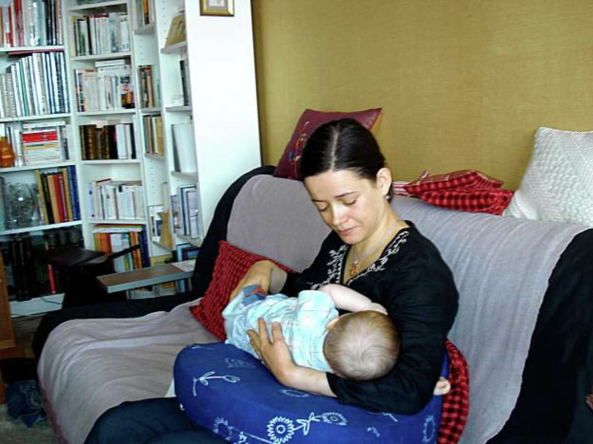 University professor Nathalie Martiniere nurses her 6- month-old boy, Francois in her Paris apartment in July. Martiniere has hired a full-time nanny to care for her infant this fall, when she resumes her commute by train from Paris to Limoges, 215 miles away.