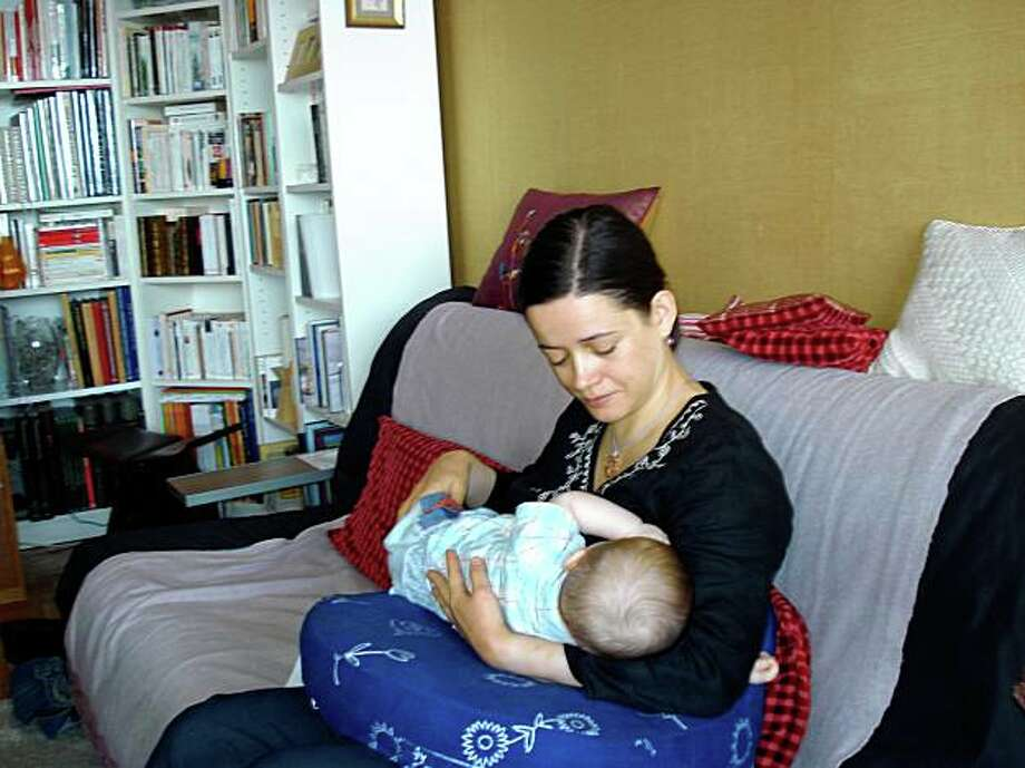 "University professor Nathalie Martiniere nurses her 6- month-old boy, Francois in her Paris apartment in July. Martiniere has hired a full-time nanny to care for her infant this fall, when she resumes her commute by train from Paris to Limoges, 215 miles away. ""We have acceptable day care — and you get help from the government if you choose to have someone to care for your child or you put him in the creche, ""or nursery school, she says. Photo: Elizabeth Bryant, Special To The Chronicle"