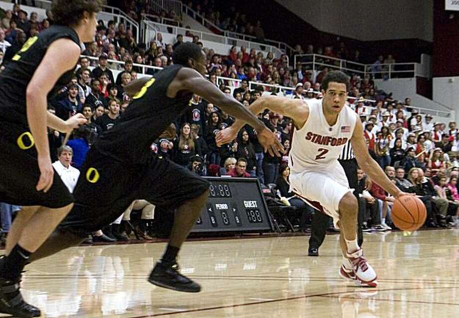 Landry Fields dribbles upcourt into Oregon's Drew Wiley and Jeremy Jacob, from left, at Stanford's basketball game against Oregon in Palo Alto on Saturday. Photo: Adam Lau, The Chronicle