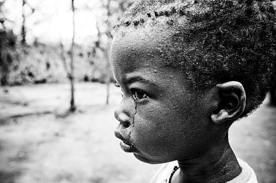 A child cries in front of a feeding center in Kakuma refugee Camp, Kakuma, Kenya on January, 2008.  Kenya has declared a national emergency after drought conditions and disruptions to agriculture due to post election violence have left millions in danger of starvation. This image is part of the entry from Zoriah Miller that won the 2009 Photo Philanthropy Activist Award Grand Prize in the Professional category.  It was shot on behalf of the International Rescue Committee at their Kakuma Rescue Camp hospital in Kenya. Photo: Zoriah Miller/IRC, Photo Philanthropy