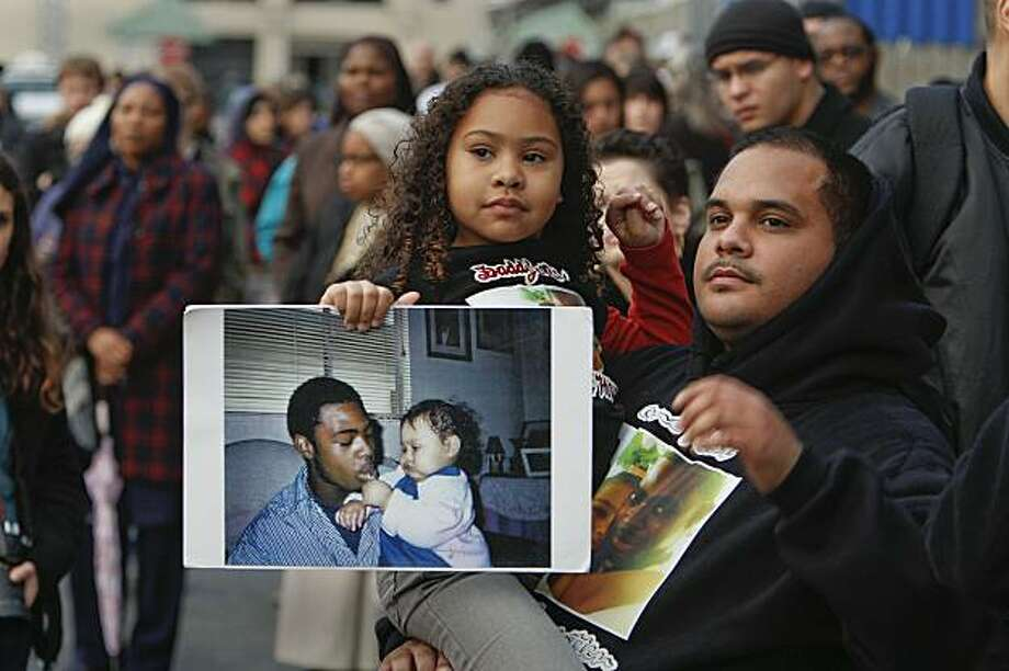 Tatiana Grant, 5-years-old, holds a picture of her and her father, Oscar Grant, as she and her uncle Danny Pangelina join a crowd of family, friends and supporters, gathered at the Fruitvale BART station in Oakland, Ca., for a vigil to remember Grant on Friday January 1, 2010, exactly a year after he was shot and killed, early New years Day 2009. Photo: Michael Macor, The Chronicle