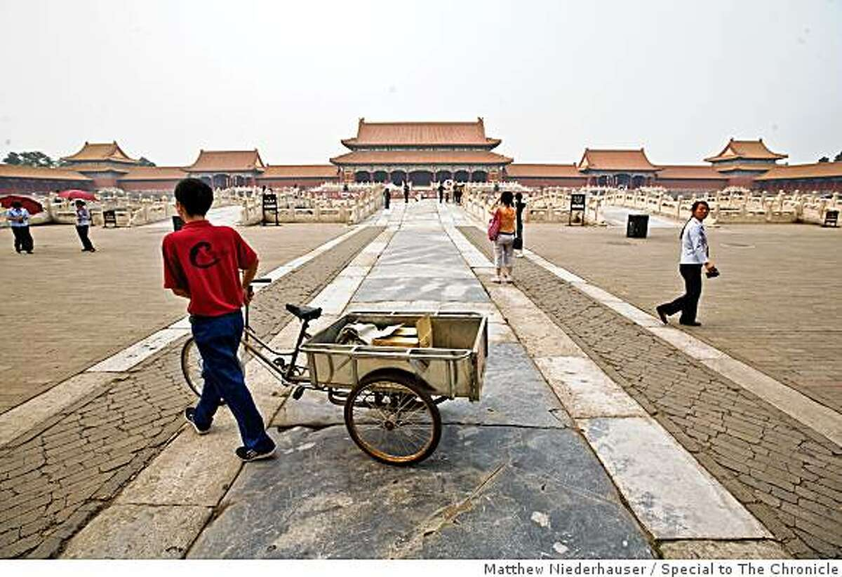A worker pushes his tricycle through the Forbidden City.