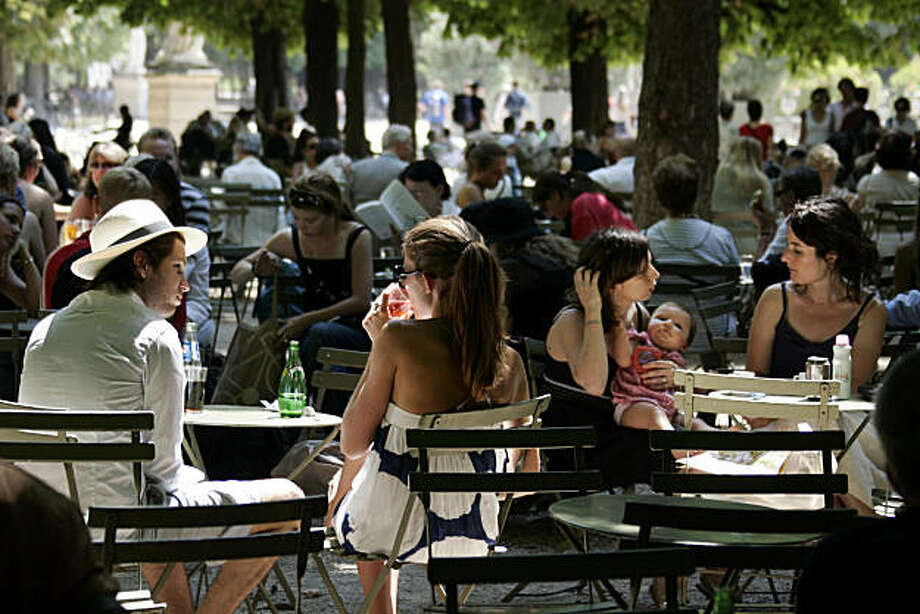 Parisians relax in the Luxembourg gardens, in Paris, France, Wednesday, July 23, 2008. Paris may be the most visited city in the world, it's also one of the most expensive. Yet for those in the know, there are plenty of cheap, and even free ways to enjoy the city. You can go into the Luxembourg gardens, where Parisians hang out by the fountain, get a tan, and listen to free music on summer weekends. (AP Photo/Francois Mori) Photo: Francois Mori, AP