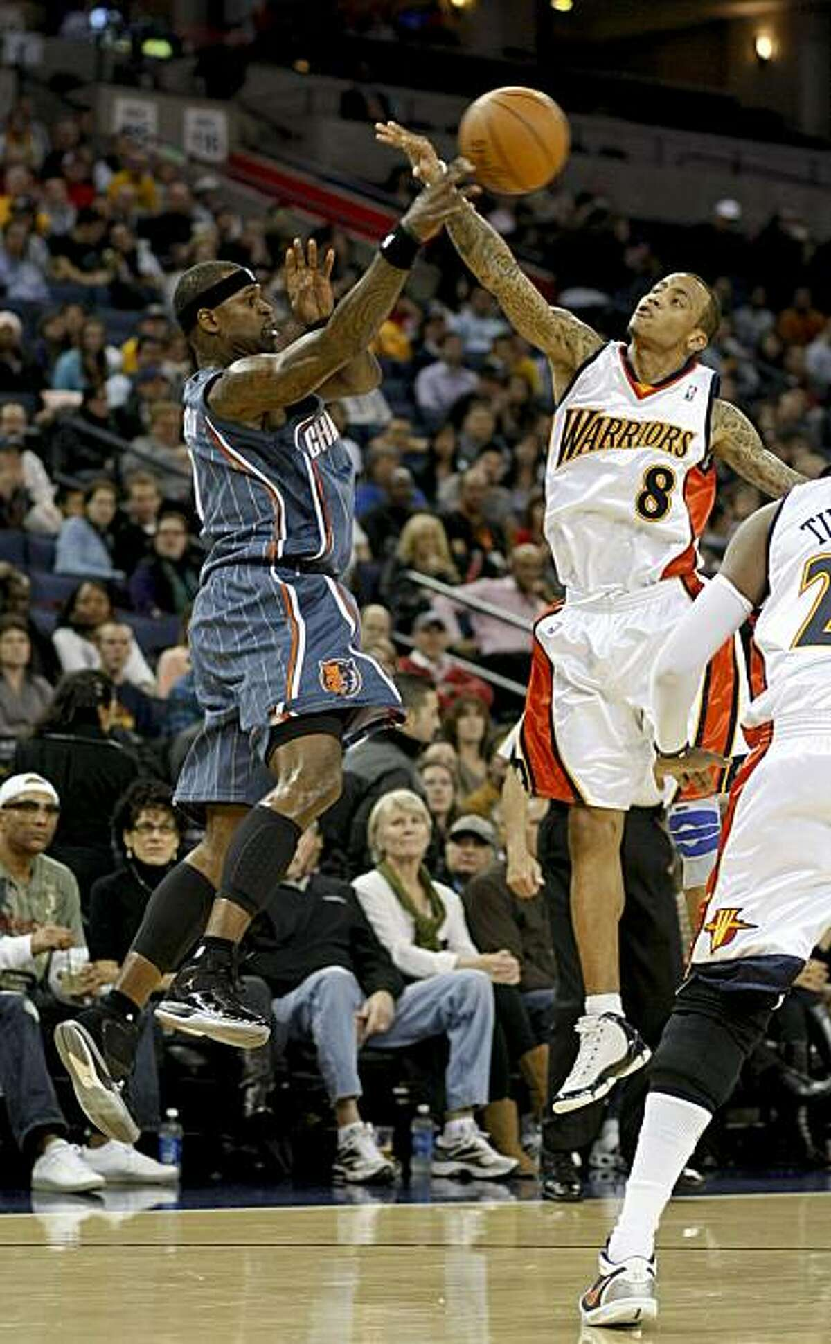 Charlotte Bobcats' Stephen Jackson with a pass over Golden State Warriors' Monta Ellis in the first half as the Golden State Warriors take on the Charlotte Bobcats in Oakland on Friday.