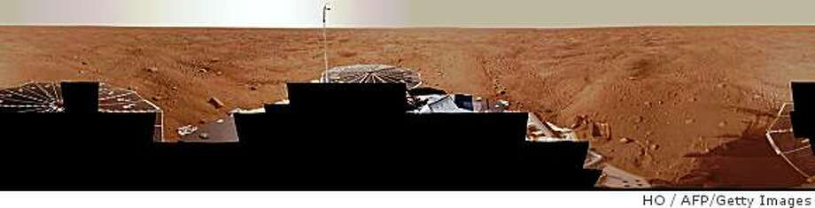 "This NASA handout image obtained on August 5, 2008 shows a view that combines more than 400 images taken during the first several weeks after NASA's Phoenix Mars Lander as it arrived on an arctic plain at 68.22 degrees north latitude, 234.25 degrees east longitude on Mars. The full-circle panorama in approximately true color shows the polygonal patterning of ground at the landing area, similar to patterns in permafrost areas on Earth. The center of the image is the westward part of the scene. Trenches where Phoenix's robotic arm has been exposing subsurface material are visible in the right half of the image. The spacecraft's meteorology mast, topped by the telltale wind gauge, extends into the sky portion of the panorama. The Phoenix lander's analysis of recent soil samples taken on Mars has found possible traces of perchlorate, a highly oxidizing substance detrimental to life, NASA said on August 4, 2008. Two separate soil samples were analyzed within the last month by two onboard Phoenix instruments, ""suggesting one of the soil constituents may be perchlorate,"" NASA said in a statement stressing the preliminary quality of the tests. ""We are committed to following a rigorous scientific process. While we have not completed our process on these soil samples, we have very interesting intermediate results,"" said Peter Smith, Phoenix's principal investigator at the University of Arizona, Tucson. AFP PHOTO/NASA/JPL-CALTECHUNIVERSITY OF ARIZONA/TEXAS A&M UNIVERSITY=RESTRICTED TO EDITORIAL USE =GETTY OUT= (Photo credit should read HO/AFP/Getty Images) Photo: HO, AFP/Getty Images"