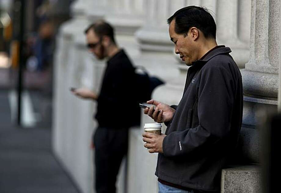 Everyone on the street is looking down at their phone... Just kidding. That's every day in San Francisco.  Photo: Michael Macor, The Chronicle