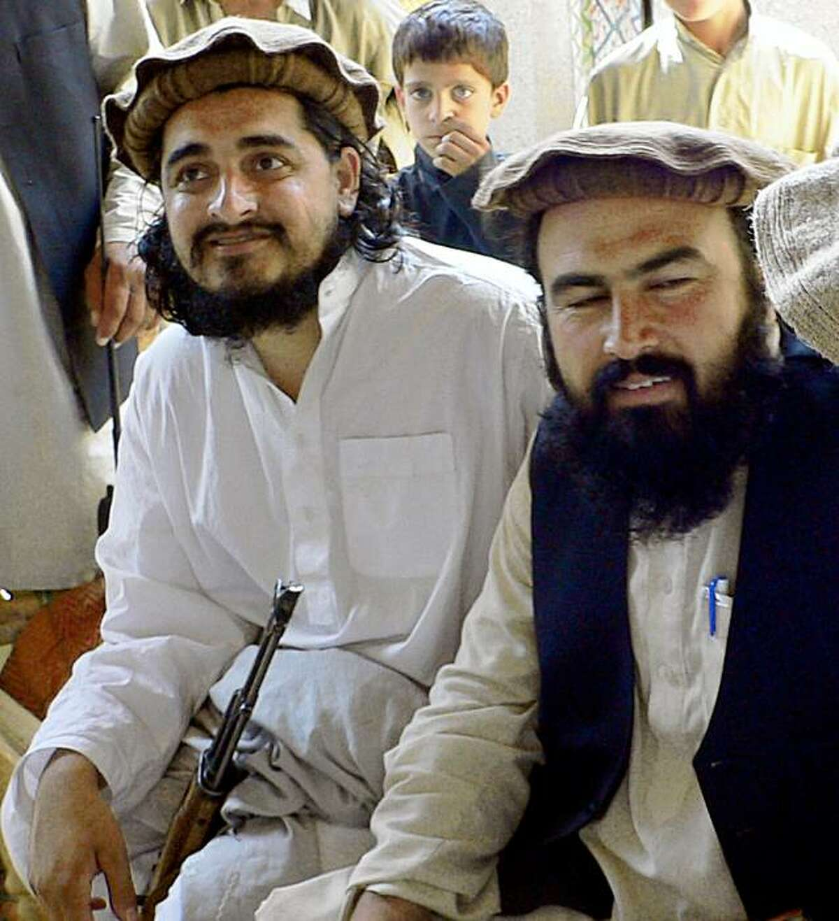 In this photograph taken on October 4, 2009 shows new Pakistani Taliban chief Hakimullah Mehsud (L) sits with his commander Wali-ur Rehman (R) during his meeting with local media representatives in Sararogha area of South Waziristan along the Afghanistan border. Hakimullah Mehsud appeared in front of the local media persons on October 4, dispelling rumours of his death and vowing