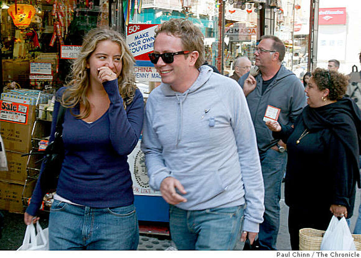 French tourists Margot Icher, left, and her uncle Thomas Icher laugh as they walk past a Chinatown souvenir shop in San Francisco, Calif., on Wednesday, Aug. 6, 2008. Behind them are Margot's parents Bruno and Laure Icher. European tourists are flocking to San Francisco to take advantage of favorable exchange rates.