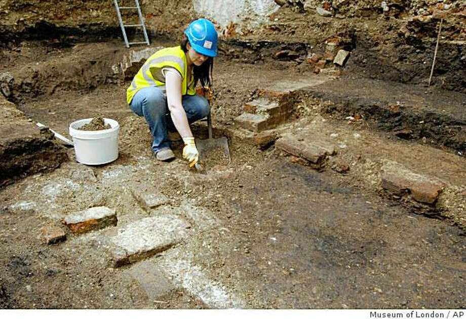 In this undated photo made available in by the Museum of London, in London, Wednesday Aug. 6, 2008, an archeologist works on uncovering the remains of one of London's earliest theatres where a young William Shakespeare is thought to have trod the boards. The find, believed to be a section of one of London's earliest playhouses, was unearthed as the site was being prepared for the construction of a new theatre. Experts have thought for many years that an open air playhouse, called The Theatre, stood in the Shoreditch area of London but its exact location had remained uncertain. A young William Shakespeare trod the boards at the theatre, which opened in 1576, as part of The Lord Chamberlain's Men company of players.(AP Photo/Museum of London, ho) **NO SALES:** Photo: Museum Of London, AP
