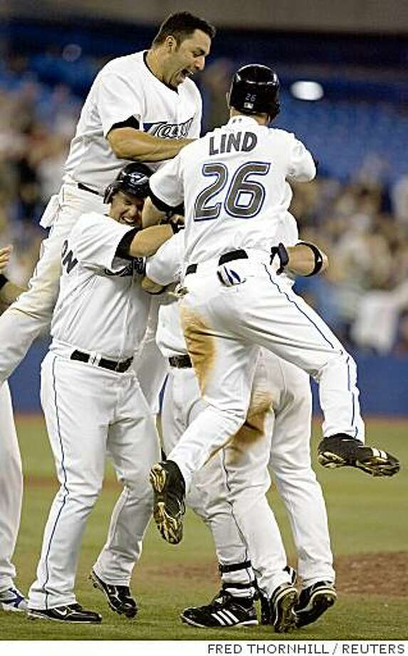 Toronto Blue Jays' Kevin Mench is mobbed by team mates after he hit a walk off double to beat the Oakland Athletics in their American League MLB baseball game in Toronto August 5, 2008. Mench is under the pile of players after he rounded first base.  REUTERS/Fred Thornhill  (CANADA) Photo: FRED THORNHILL, REUTERS