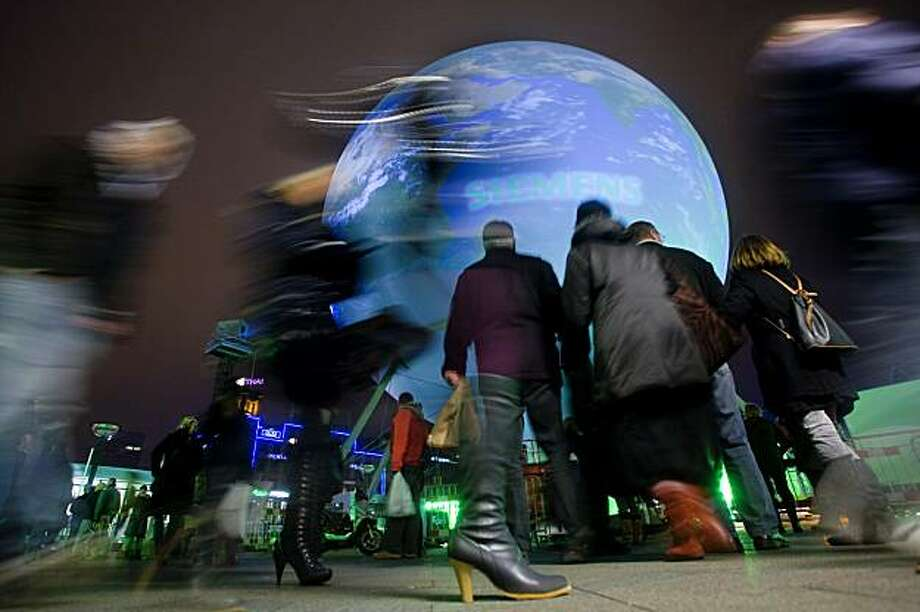 People walk by the gigantic earth globe on the town square in Copenhagen on December 6, 2009, on the eve of the opening of the United Nations Climate Conference 2009. 100 heads of state or government will participate in the UN-led Climate Change Conference in Copenhagen from 7 to 18 December 2009. AFP PHOTO / Mikkel Moeller Joergensen/SCANPIX DENMARK (Photo credit should read Mikkel Moeller Joergensen/AFP/Getty Images) Photo: Mikkel Moeller Joergensen, AFP/Getty Images