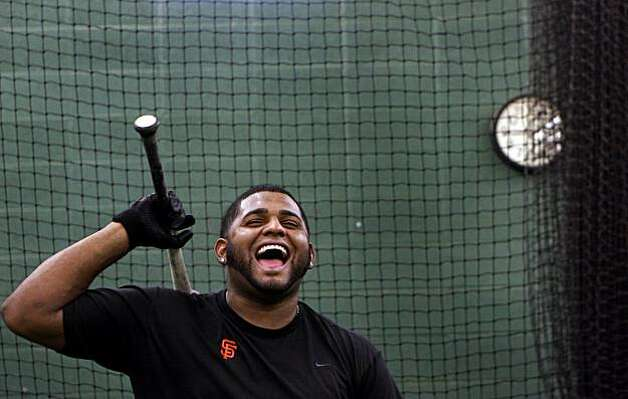 Sandoval laughs with his brother Michael as they work out in the batting cage. Photo: Joshua Lott, Special To The Chronicle