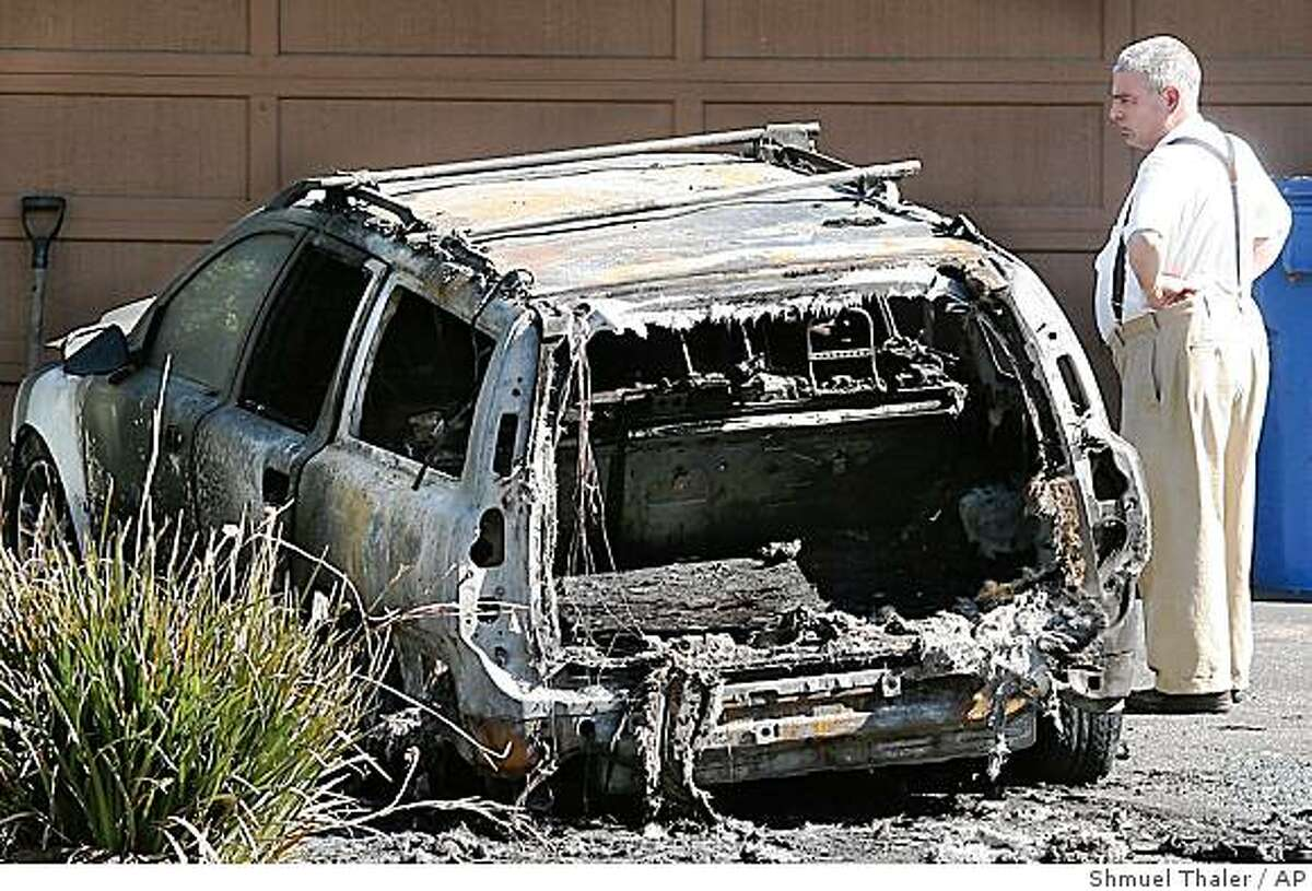 A pedestrian on Dickens Way in Santa Cruz, Calif. looks at the burned wreckage of a car that was destroyed by a fire bomb on Saturday, Aug. 2, 2008. The FBI is investigating two bombings that targeted university scientists, the latest in a rash of attacks against biomedical researchers who experiment on animals, authorities say. (AP Photo/The Sentinel, Shmuel Thaler)