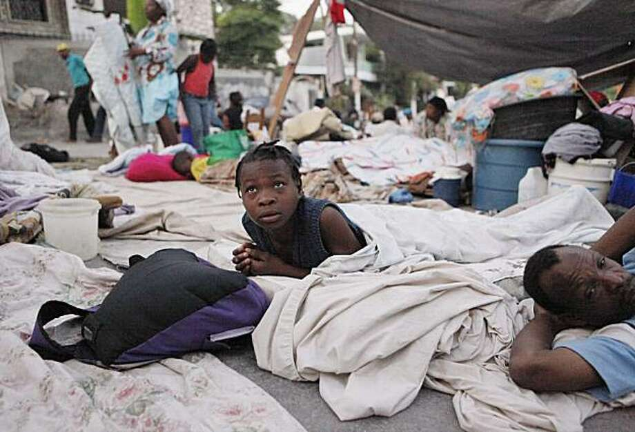 Displaced people camping in the streets awake in Port-au-Prince, Haiti, Thursday, Jan. 21, 2010. People who lost their homes in the earthquake that hit Haiti last week are sleeping in the streets for fear of aftershocks. Photo: Gerald Herbert, AP