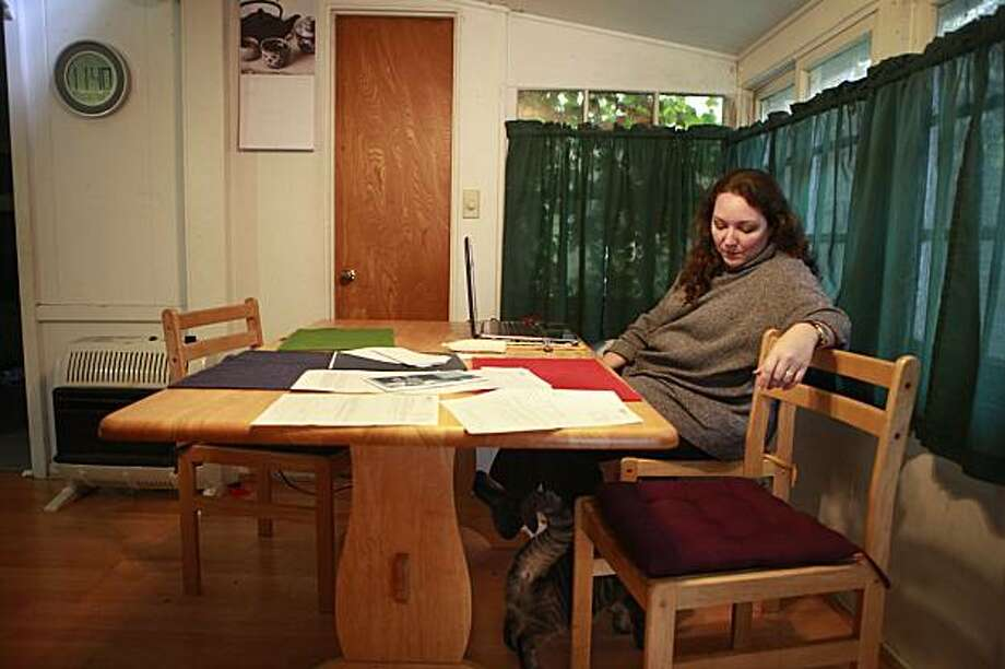 Meera Collier-Mitchell talks to her cat Piper in her dining room at home in Boulder Creek, Calif on Thursday January 7, 2010. Collier-Mitchell has been out of work for more than a year and has had trouble getting in touch with EDD's call center and received two contradictory letters that arrived on the same day. One was a Notice of Unemployment Insurance Award and the other was a Notice of Determination of Invalid Claim, Section 1277. Photo: Lea Suzuki, The Chronicle