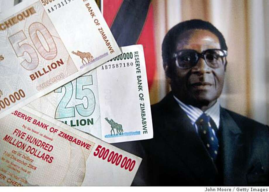 BULAWAYO, ZIMBABWE - (FILE)  The official portrait of President Robert Mugabe hangs on the wall as Zimbabwaen dollar bank notes are shown June 28, 2008 at the airport in Bulawayo, Zimbabwe. To combat Zimbabwe's hyper-inflated economy ten zeros have been removed from currency July 30, 2008 with ten billion dollars becoming one dollar.   (Photo by John Moore/Getty Images) Photo: Getty Images