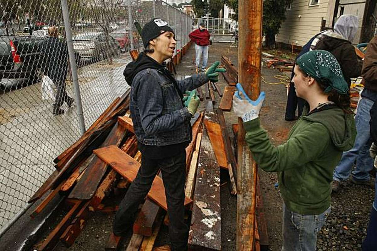 Volunteer Celina Cardenas, (left) and Ahni Hecht, (garden manager) join workers who are building the