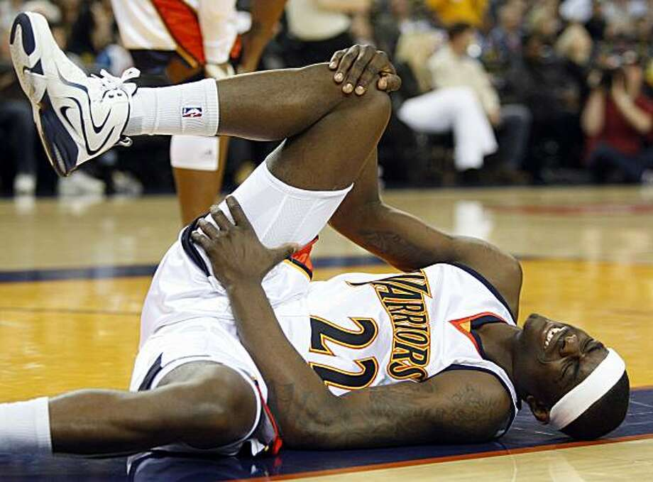 Golden State Warriors' Andrew Morrow clutches his knee in pain during the first half against the Milwaukee Bucks on Friday in Oakland. Photo: Ben Margot, AP