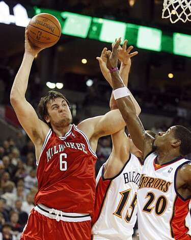 Milwaukee Bucks' Andrew Bogut, left, looks to shoot over Golden State Warriors' Cartier Martin during the first half Friday in Oakland. Photo: Ben Margot, AP