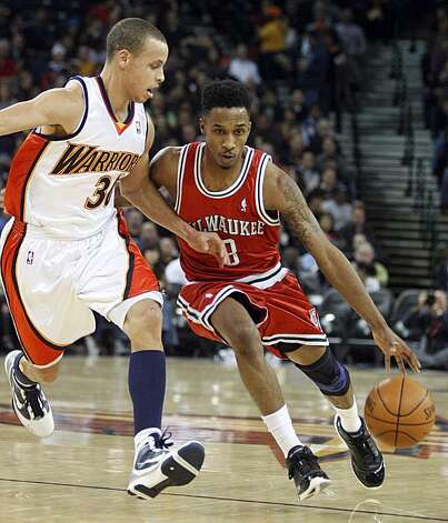 Milwaukee Bucks' Brandon Jennings, right, drives past Golden State Warriors' Stephen Curry during the first half Friday in Oakland. Photo: Ben Margot, AP