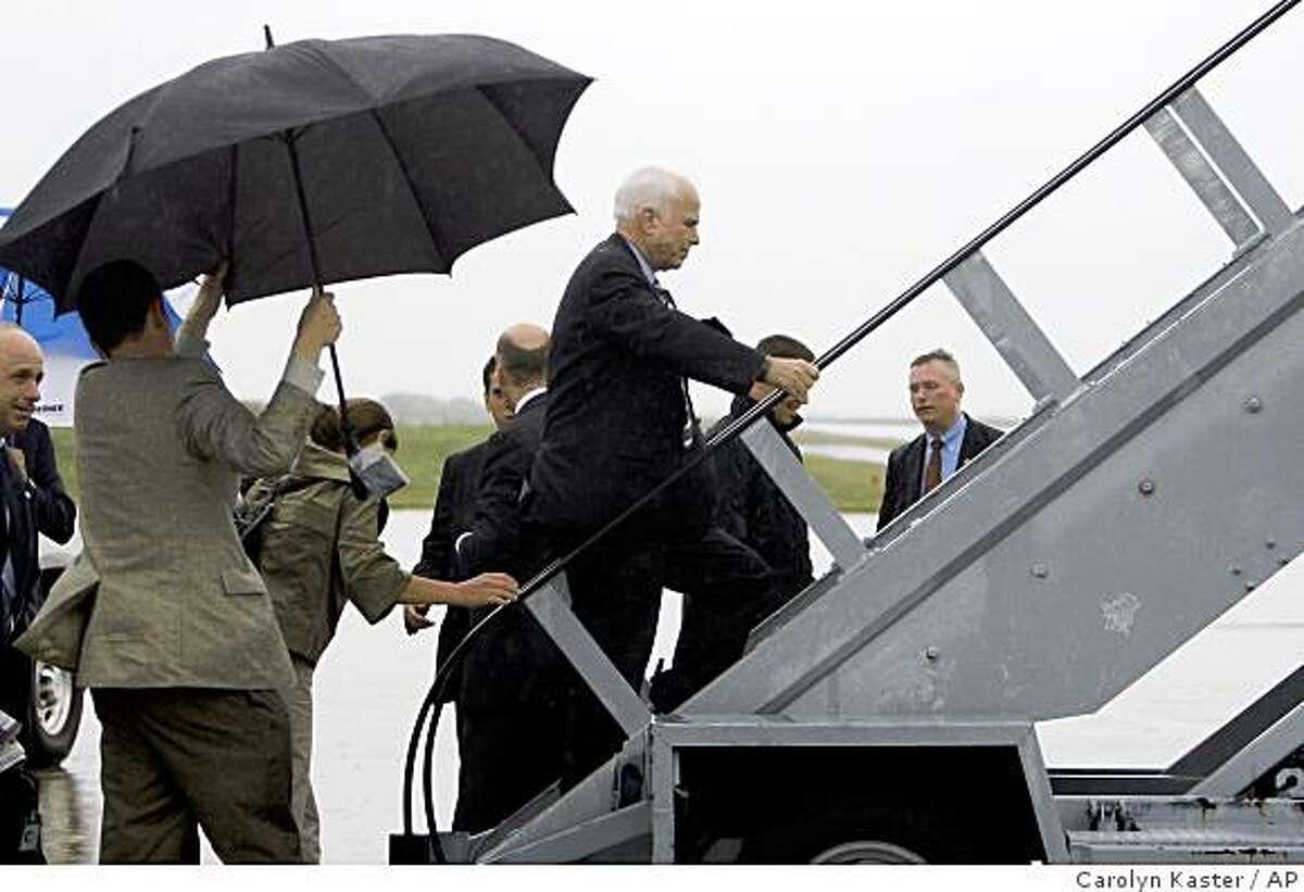 Republican presidential candidate Sen. John McCain, R-Ariz., boards his campaign plane as rain falls in Allentown, Pa., Wednesday, July 23, 2008. (AP Photo/Carolyn Kaster)
