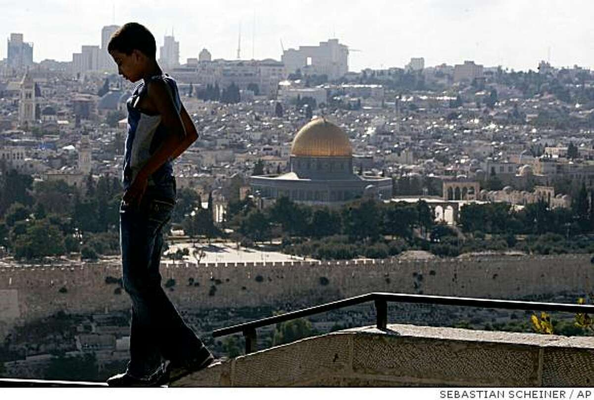 The Dome of the Rock Mosque is seen in Jerusalem's Old City, as a Palestinian boy walks on a wall on the Mount of Olives, Monday, July 28, 2008. Israeli Prime Minister Ehud Olmert backed away Monday from a target date announced with great fanfare at a U.S.-hosted Mideast peace conference last November of forging a deal with the Palestinians by year's end. The Israeli prime minister said the sides will need more time to bridge differences over Jerusalem, long the toughest sticking point in Israeli-Palestinian peacemaking. (AP Photo/Sebastian Scheiner)