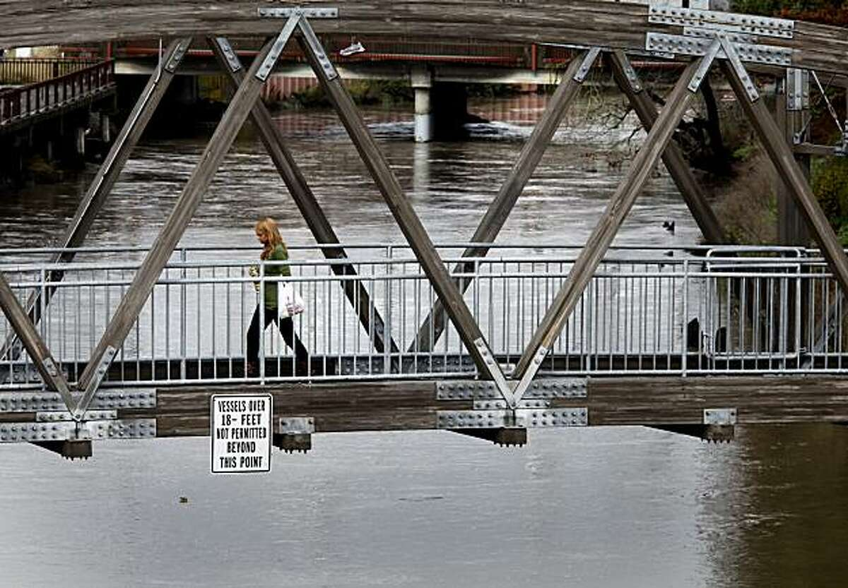 The brown Petaluma River moved well through downtown as a woman walked over a bridge over the turning basin. The latest storm to hit the Bay Area made the Petaluma River rise quickly and flooded many rural areas on the north side of Petaluma, CA.