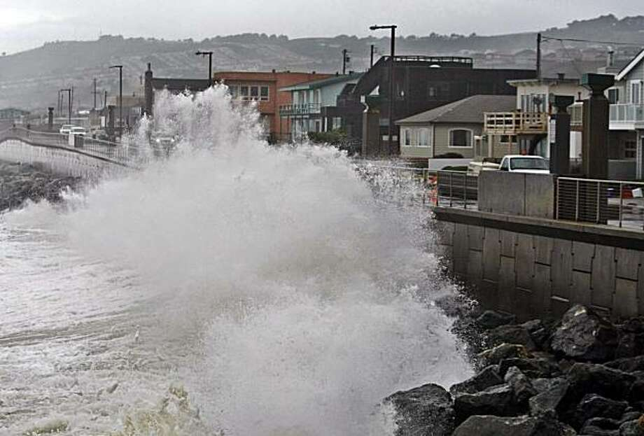 In this file photo, waves pound a wall near buildings in Pacifica during a rain storm. Photo: Paul Sakuma, AP