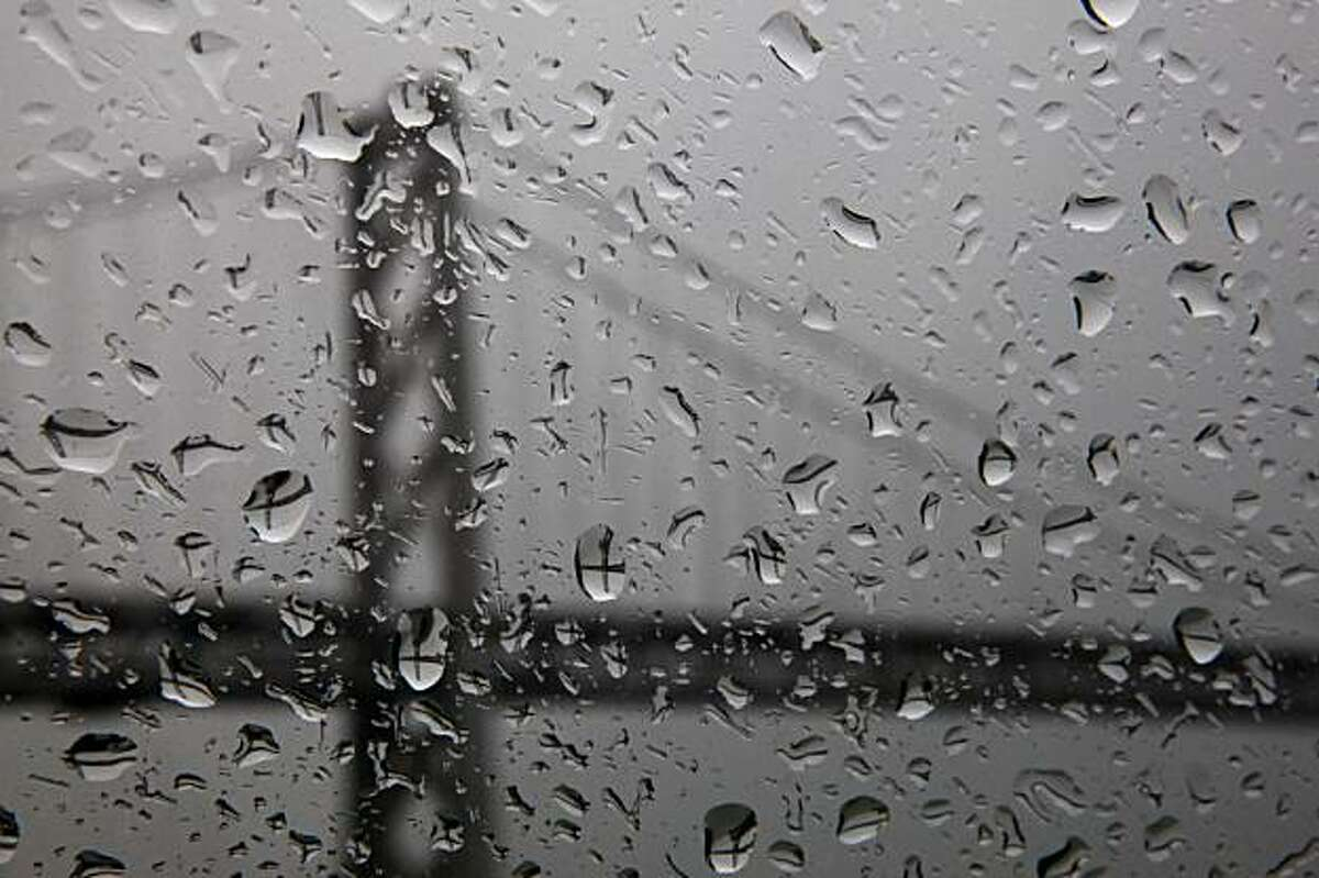 Raindrops on a window refract the image of the Bay Bridge during a rain storm on Tuesday.