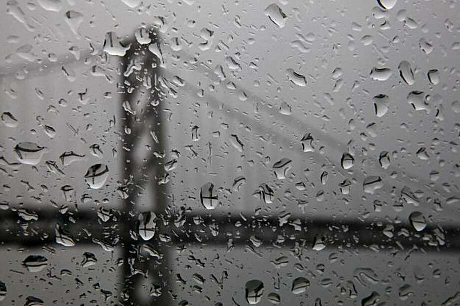 Raindrops on a window refract the image of the Bay Bridge during a rain storm on Tuesday. Photo: Carlos Avila Gonzalez, The Chronicle
