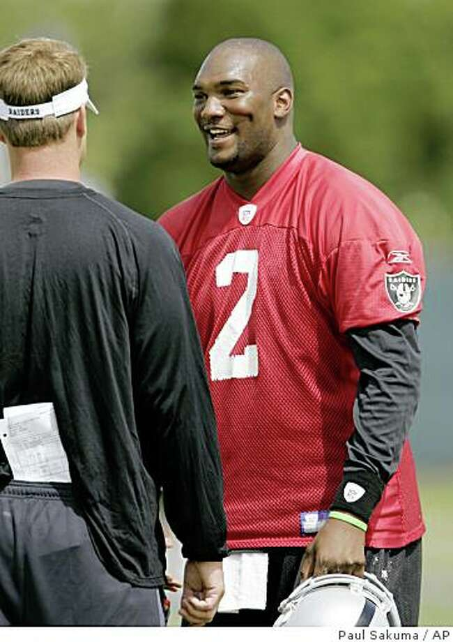 Oakland Raiders quarterback JaMarcus Russell (2) smiles at head coach Lane Kiffin, left, during football mini-camp at Raiders headquarters in Alameda, Calif., Tuesday, June 3, 2008. (AP Photo/Paul Sakuma) Photo: Paul Sakuma, AP