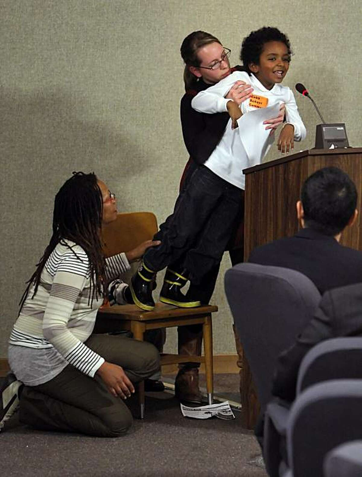 Noah Tekeste, at mic, gets a helping hand from Dr. Yvette Fagan, kneeling, and Savannah Thomson as he addresses the school board in San Francisco, Calif., on Tuesday, January 12, 2010. The school board will be deciding a controversial issue about which program to keep at Cobb Elementary -- the traditional program or the montessori. It's a huge debate among parents.