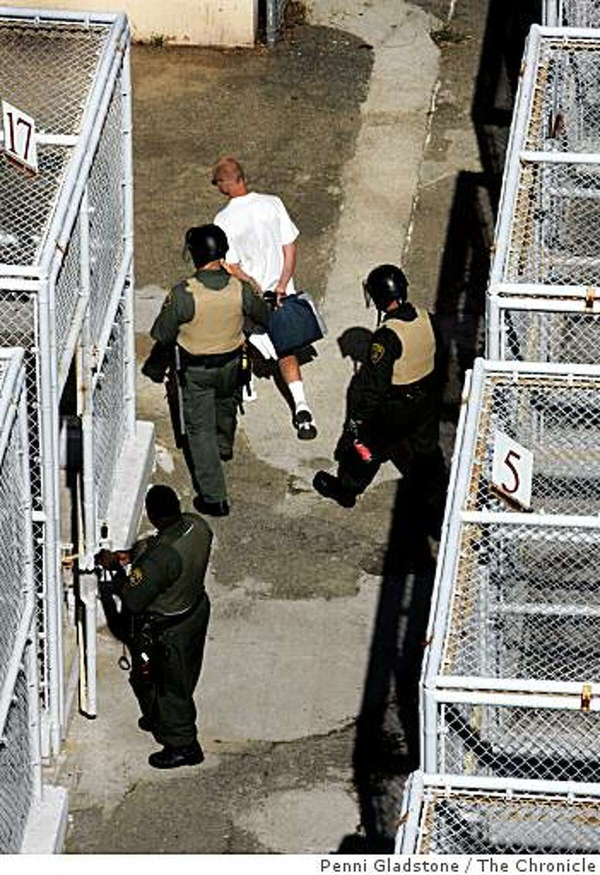 A prisoner is escorted from the death row exercise area at San Quentin prison in San Quentin, Calif. Photo by Penni Gladstone / The Chronicle